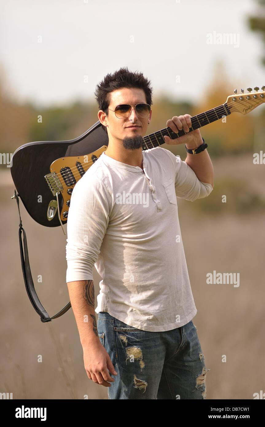 Ein Rock-Musiker tragen Sonnenbrillen tragen braune e-Gitarre auf der linken Schulter posiert im Freien in Natur Stockbild