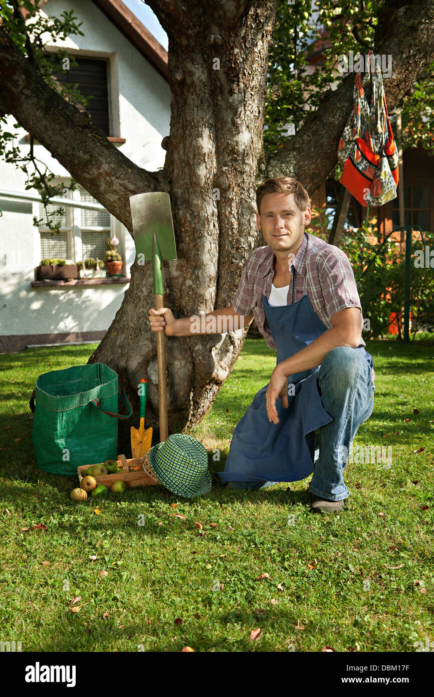 Mitte erwachsener Mann posiert neben Apfelbaum im Garten, München, Bayern, Deutschland Stockbild