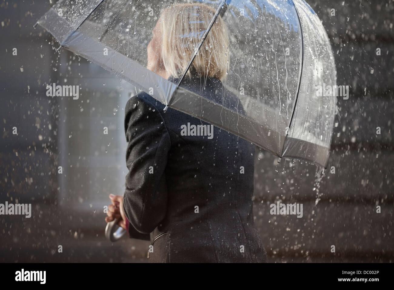 Geschäftsfrau unter Dach im Regen Stockbild