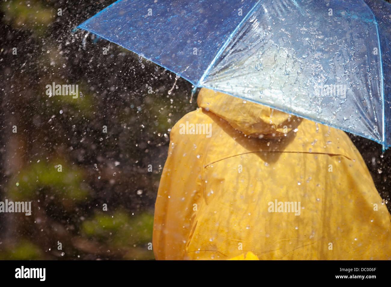 Frau unter Dach im Regen Stockbild