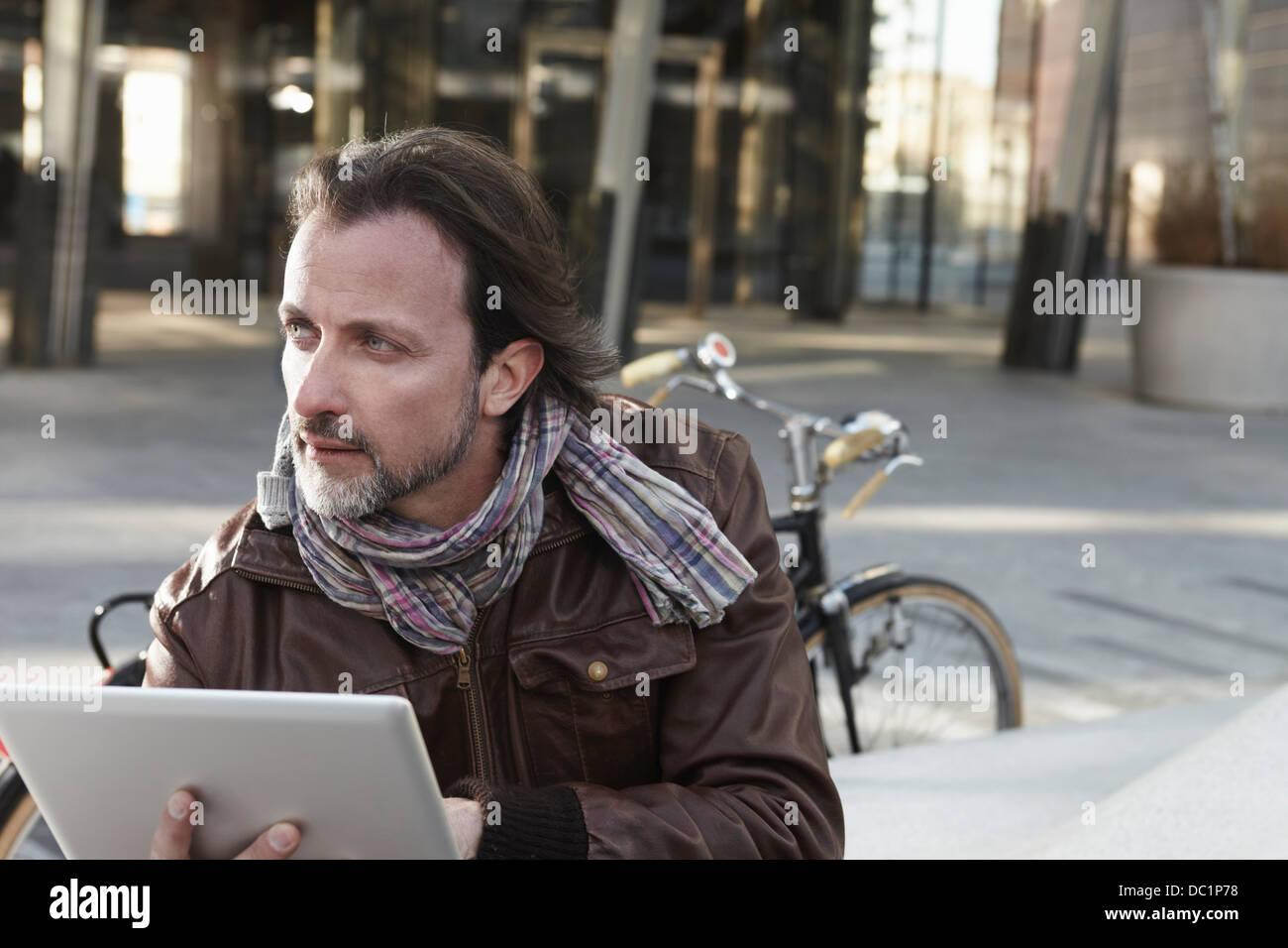 Mitte erwachsener Mann mit digital-Tablette in Stadt Stockbild