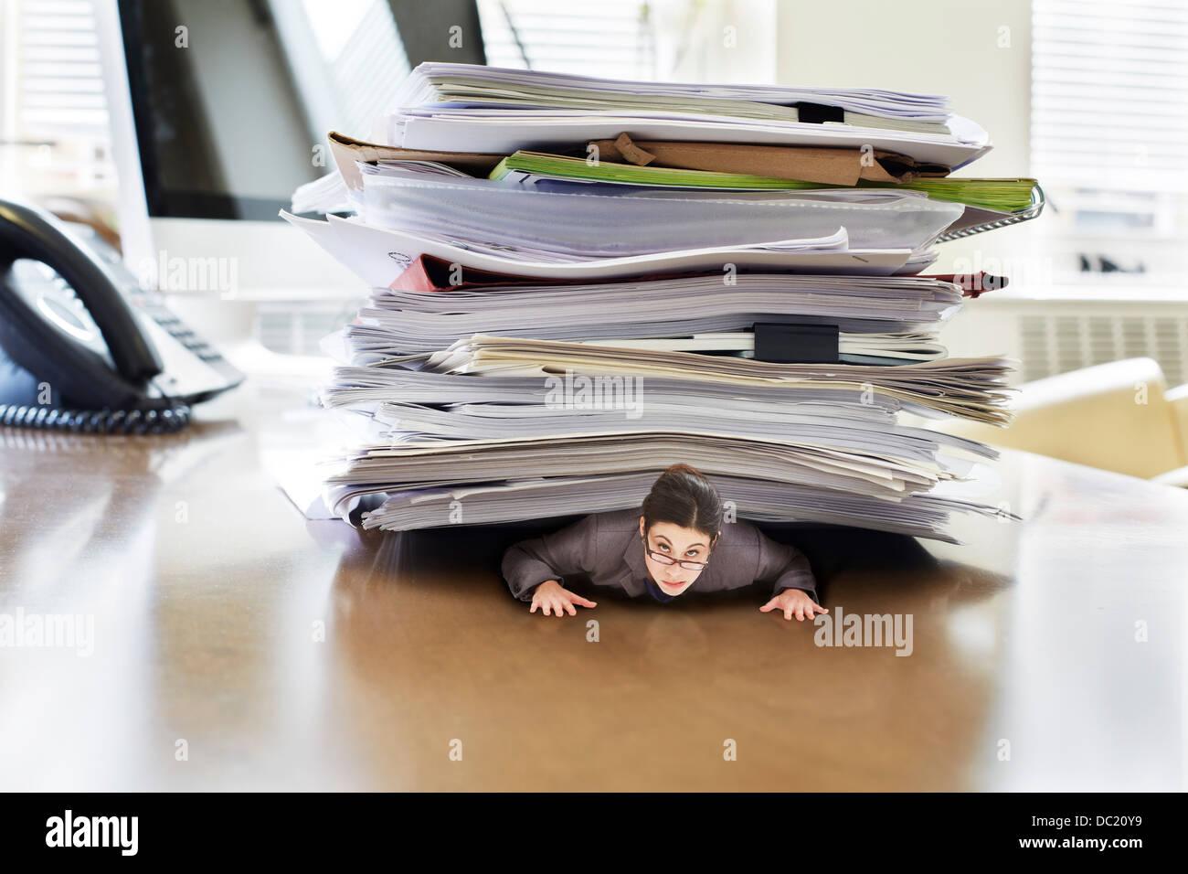 Geschäftsfrau gefangen, darunter große Papierstapel auf übergroße Schreibtisch, Porträt Stockbild