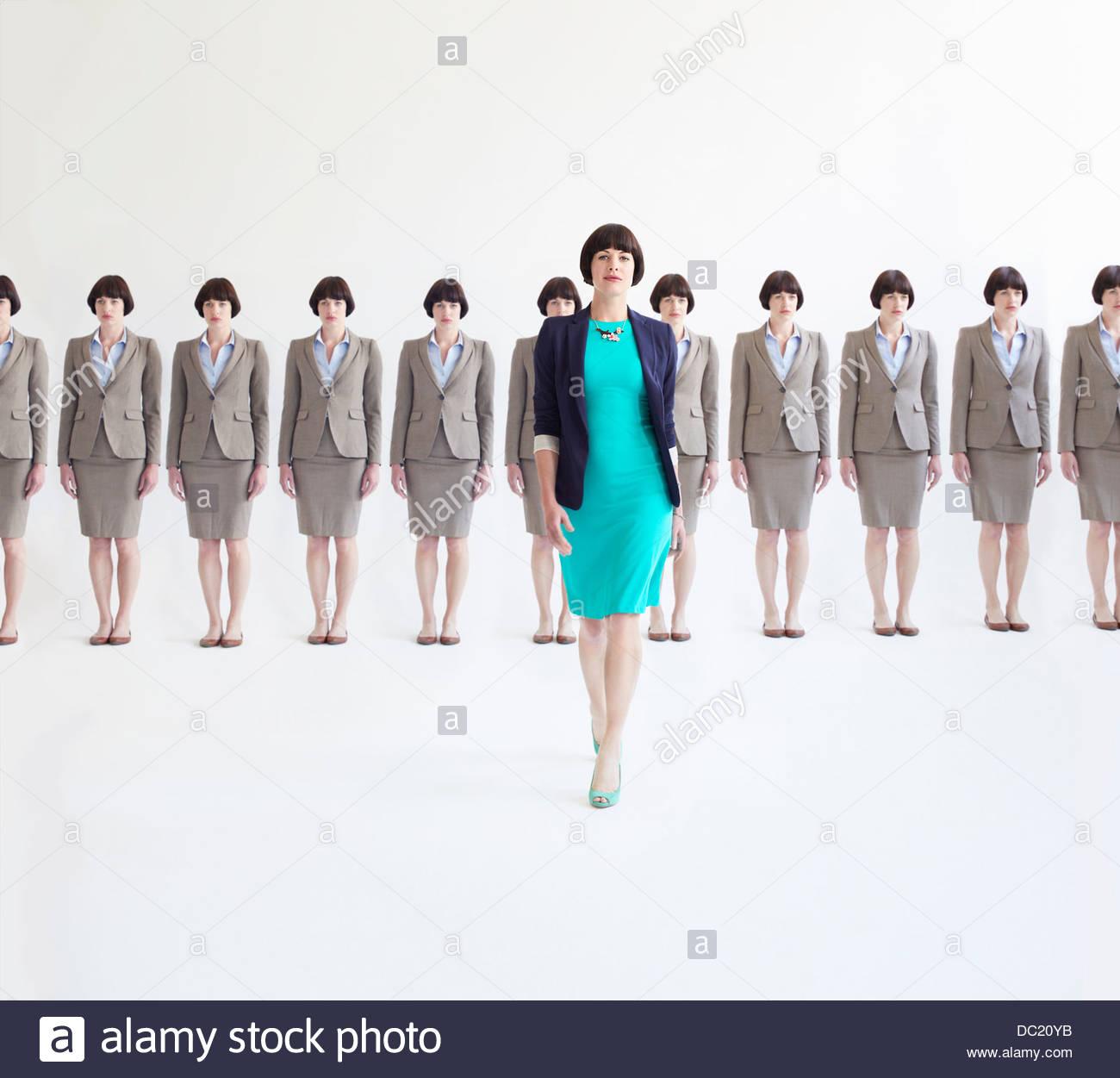 Geschäftsfrau zu Fuß entfernt von der Linie der identischen Frauen Studio gedreht Stockbild