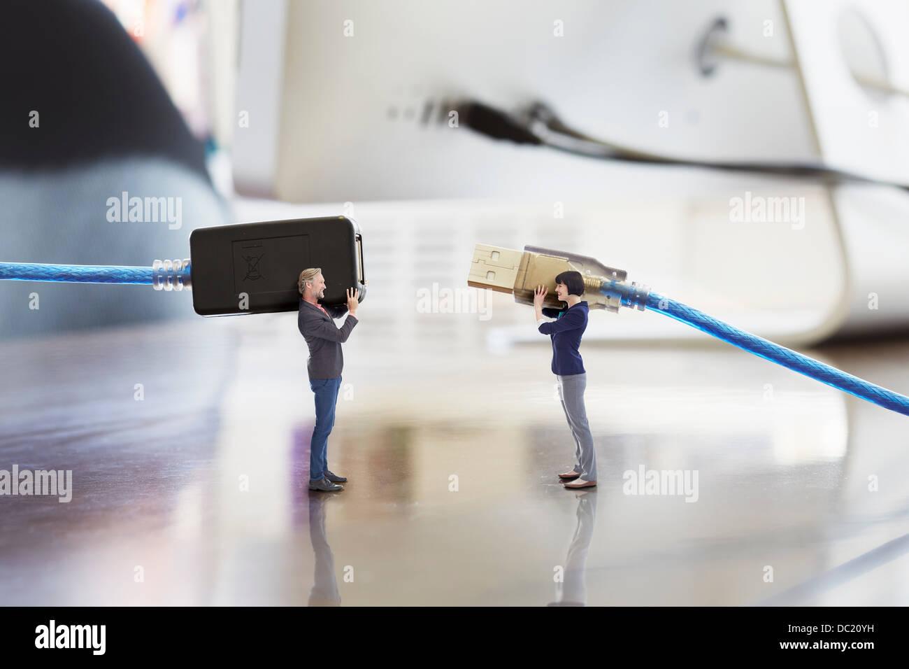 Bürokollegen halten große Computerkabel auf übergroße Schreibtisch Stockbild