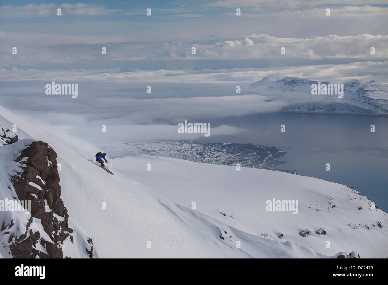 Man Snowboarden Berg an Eskifjordur, Island Stockbild