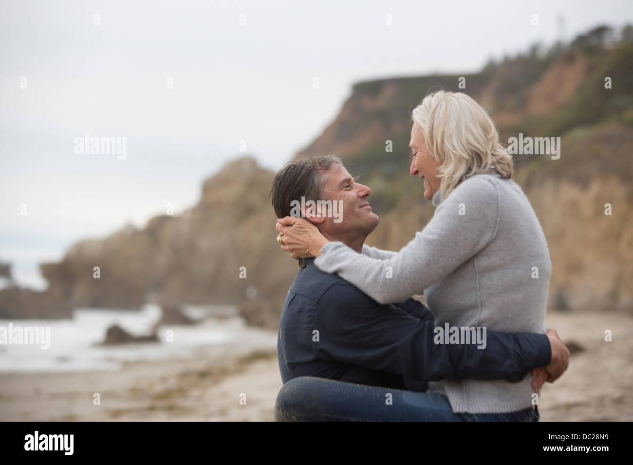 Reifer Mann heben Reife Frau am Strand Stockbild