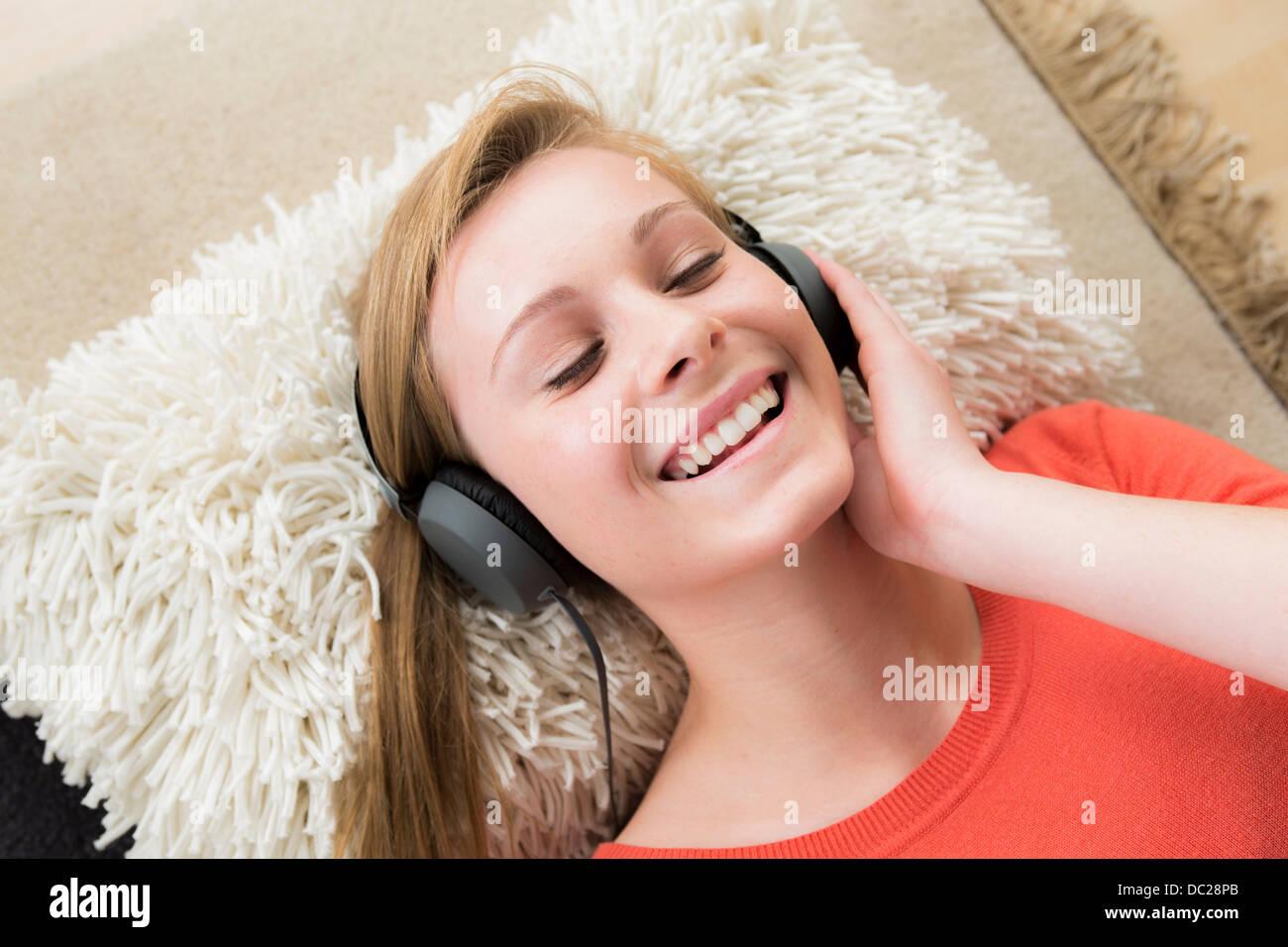 Teenager-Mädchen mit Kopfhörern mit geschlossenen Augen Stockbild