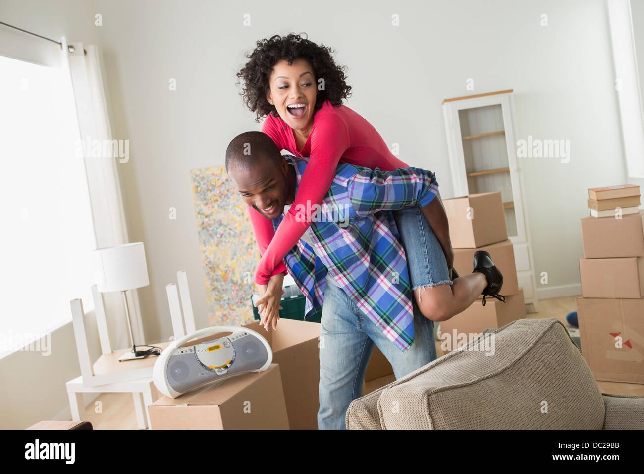 Mitte erwachsenes paar im neuen Zuhause Mann und Frau Huckepack Stockbild