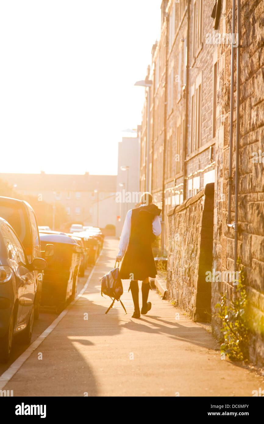 Schotte Kilt tragen, hinunter tragen einen Rucksack und Wandern eine Straße in der Abendsonne. Stockbild