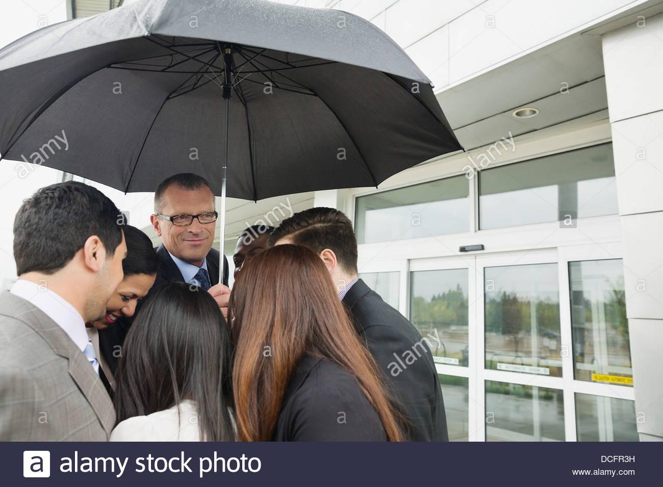 Gruppe von Geschäftsleuten Teilen einem Dach Stockbild