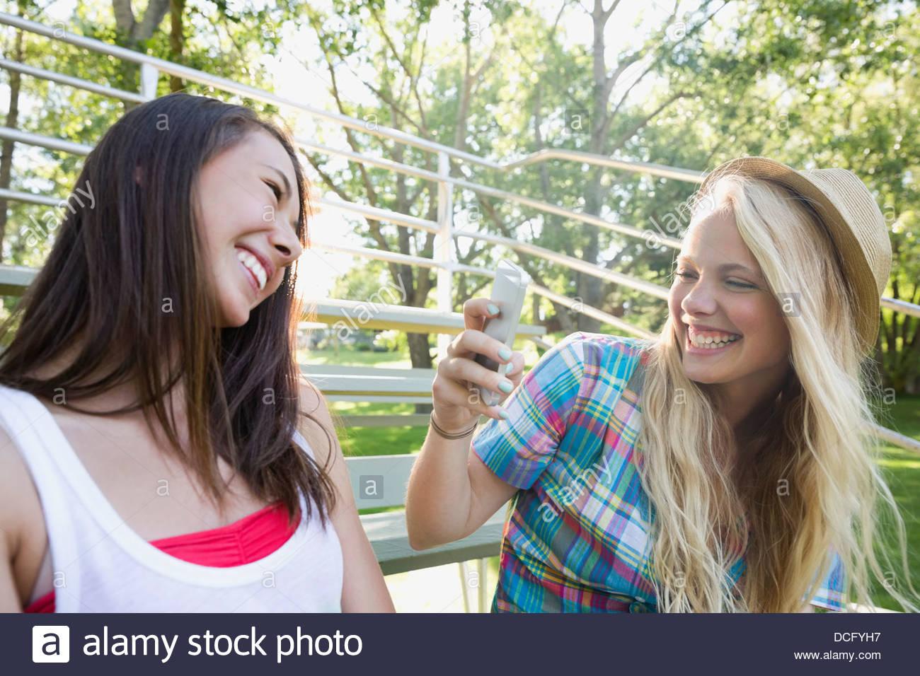 Teenager-Mädchen unter Bild von Freund auf Smartphone Stockbild
