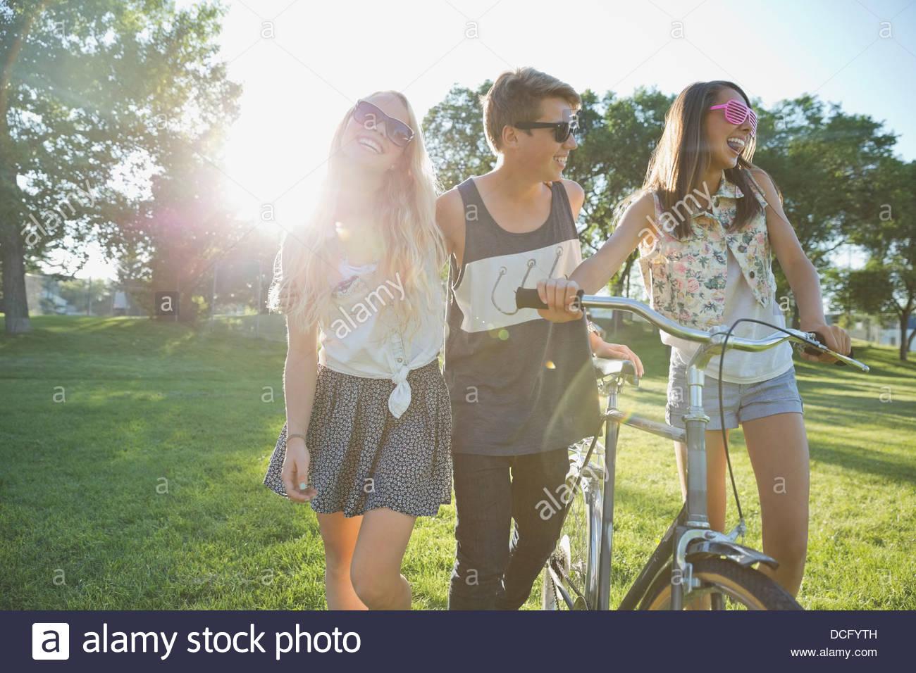 Glücklich Teenager Freunden mit dem Fahrrad, zu Fuß im park Stockbild