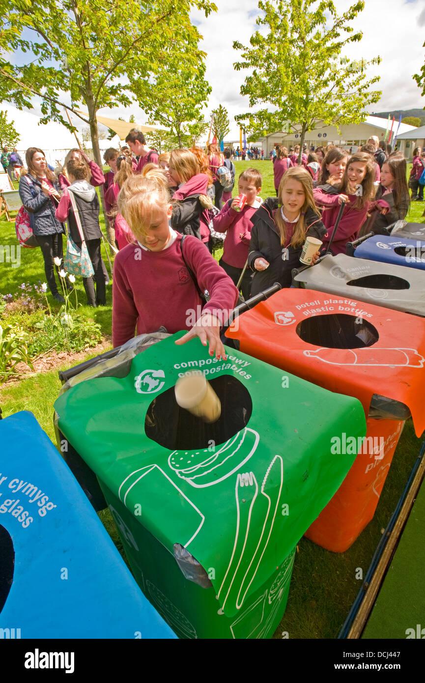 Schulkinder in der Hay Festival setzen Abfallbehälter an einem Lagerplatz für das recycling. Stockbild