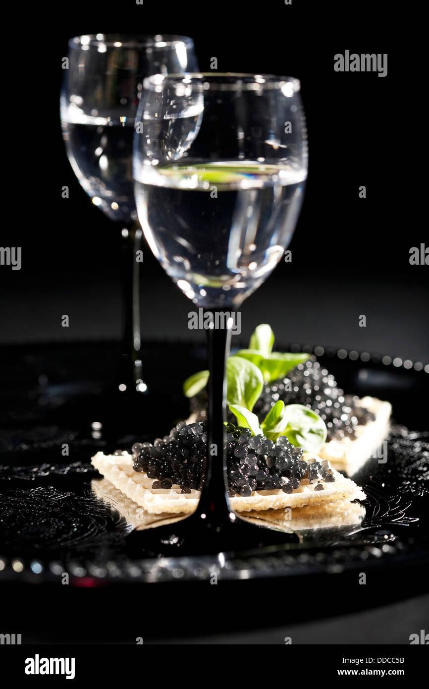 Wodka und Sandwiches mit schwarzem Kaviar auf schwarzem Hintergrund Stockbild