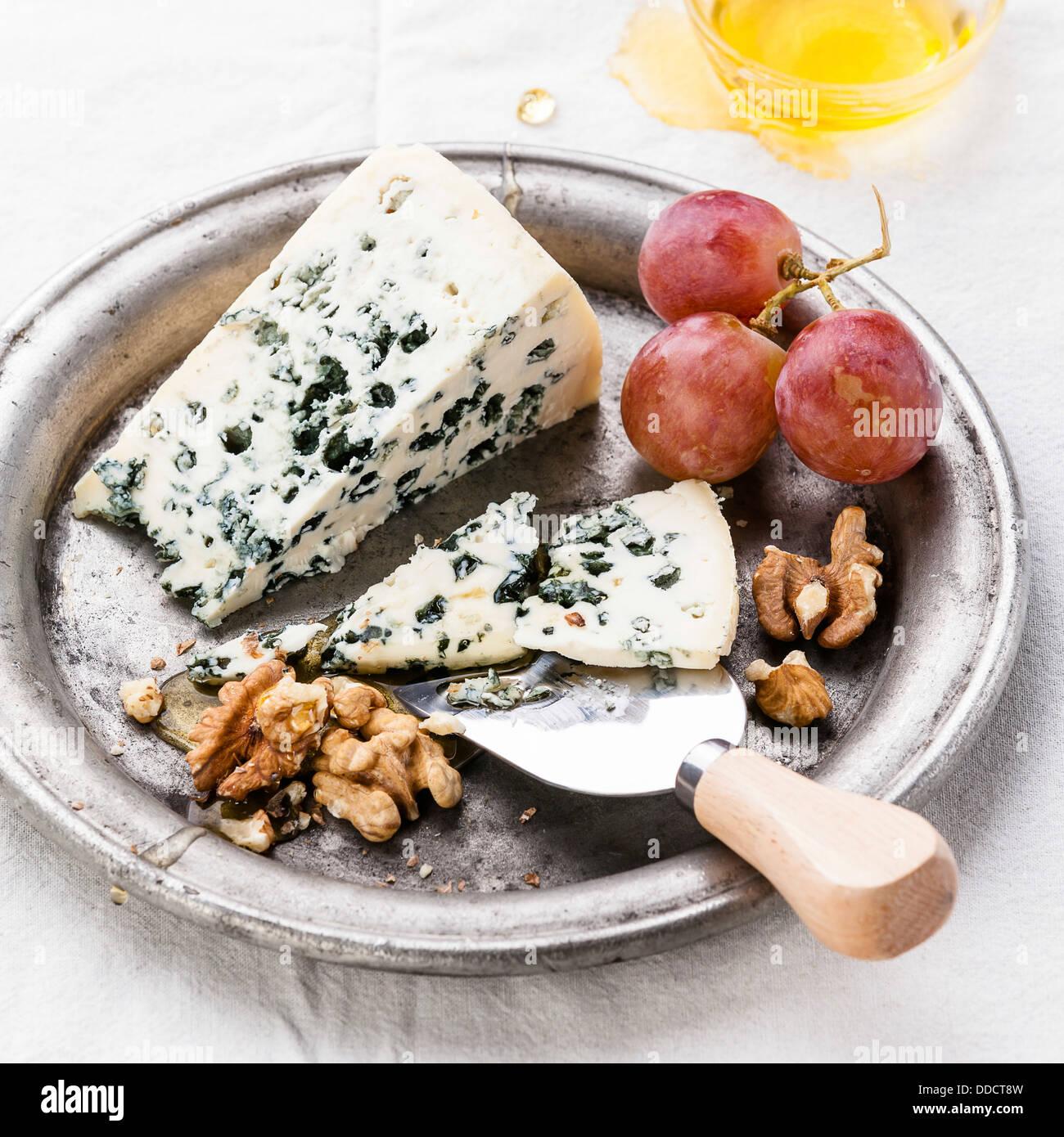 Blauschimmelkäse mit Honig, Nüssen und Trauben auf Platte Stockbild