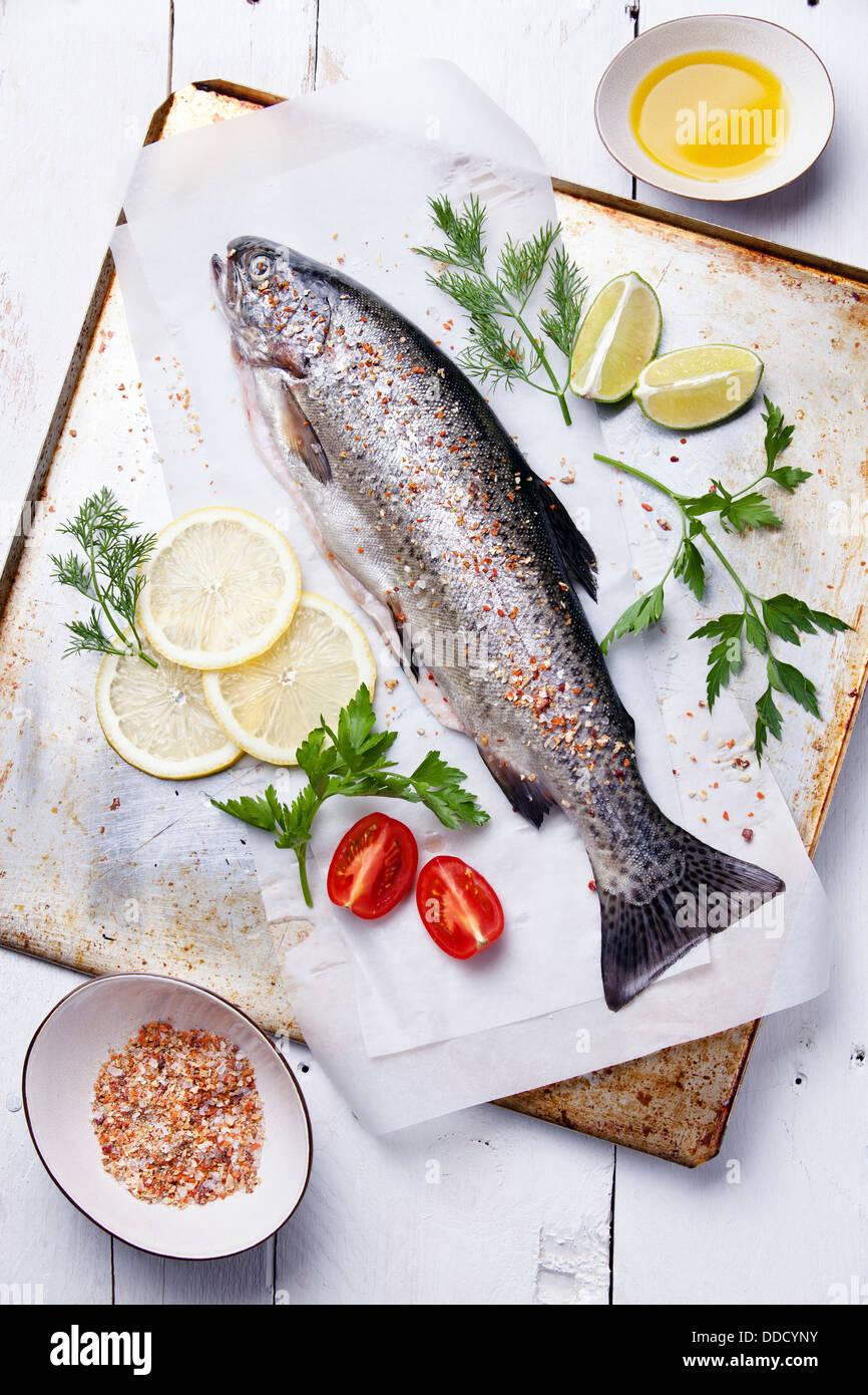 Frischen rohen Fisch Forelle mit Kräutern und Zitrone auf hölzernen Hintergrund Stockbild