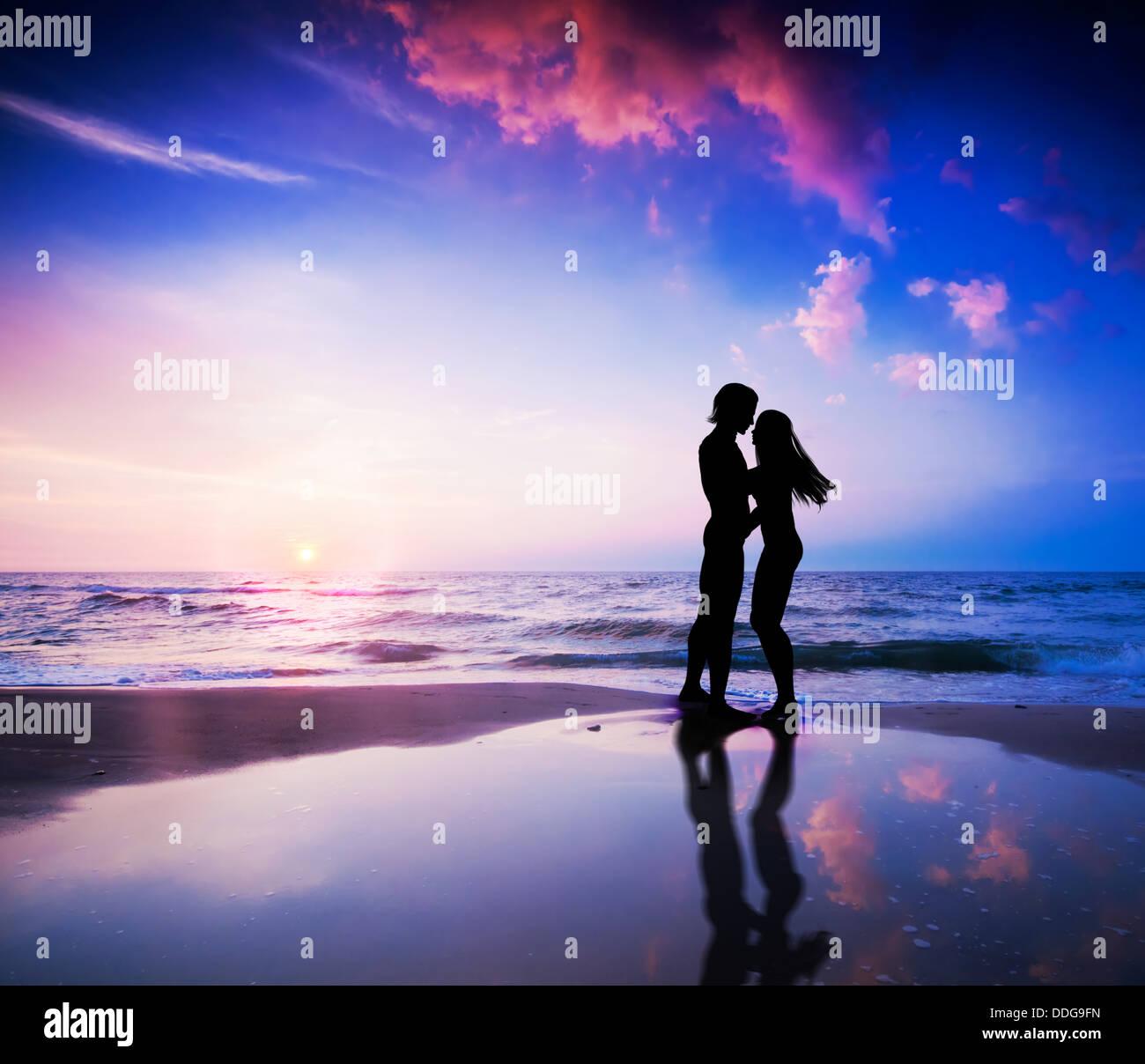 Romantisches Paar küssen am Strand bei Sonnenuntergang Stockbild