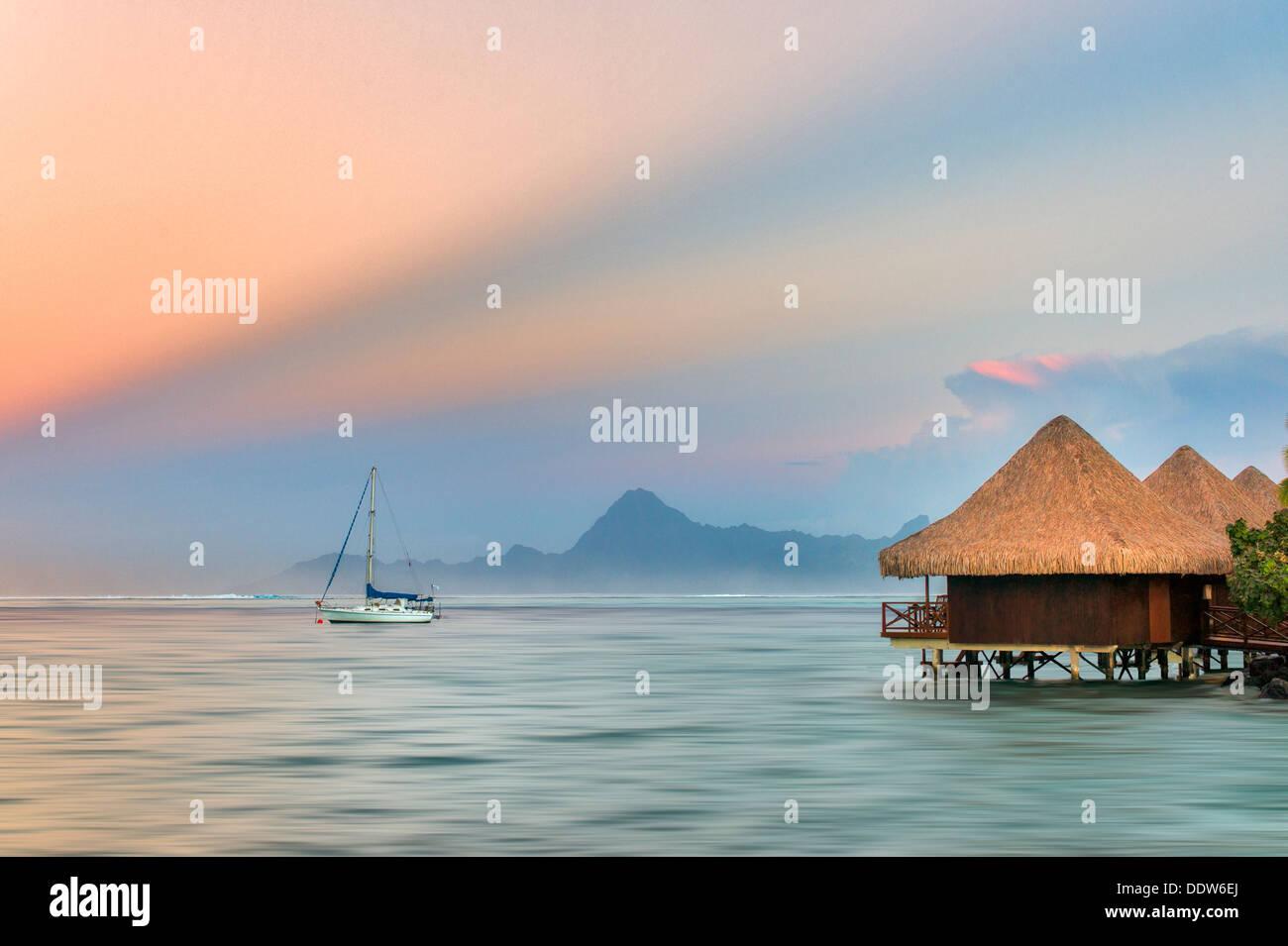 Die Bungalows über dem Wasser mit einem Segelboot und Sonnenaufgang und Moorea, Tahiti Stockbild