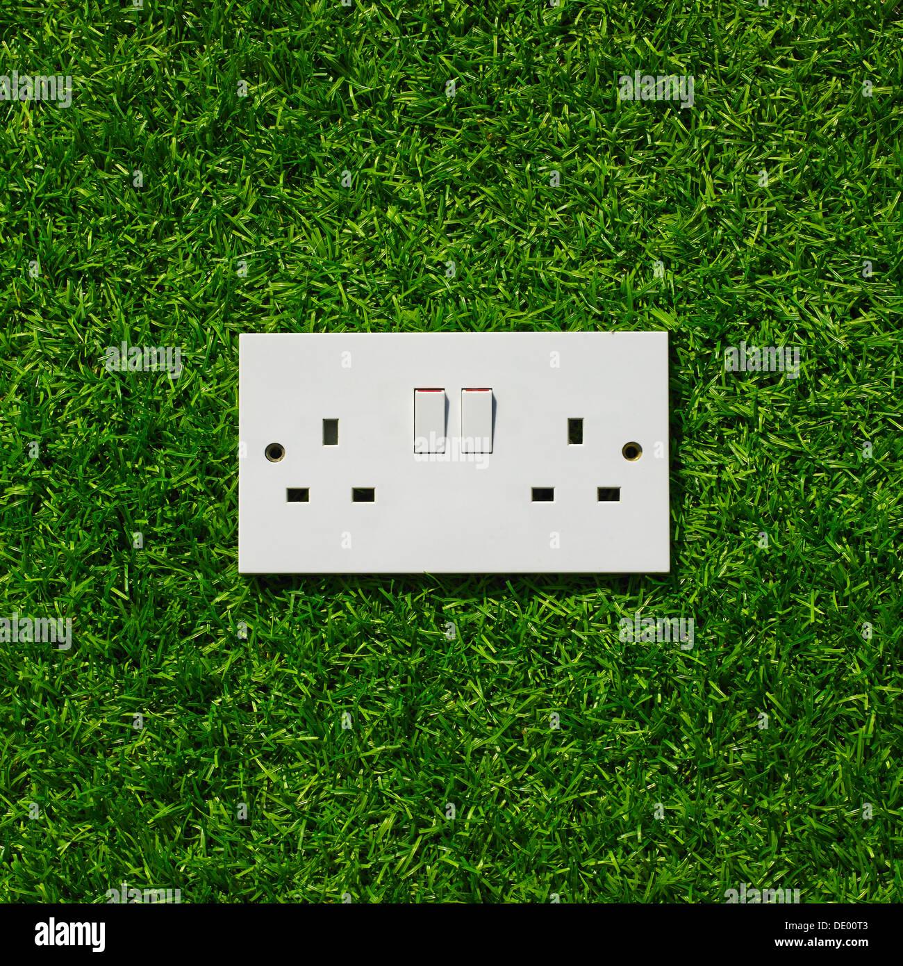 Elektrische Steckdose auf Grass Hintergrund. Stockbild