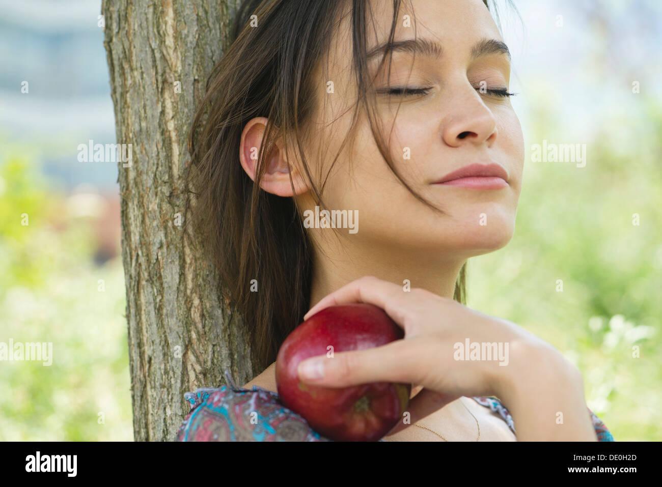 Frau entspannen im Freien mit geschlossenen Augen, mit Apfel Stockbild