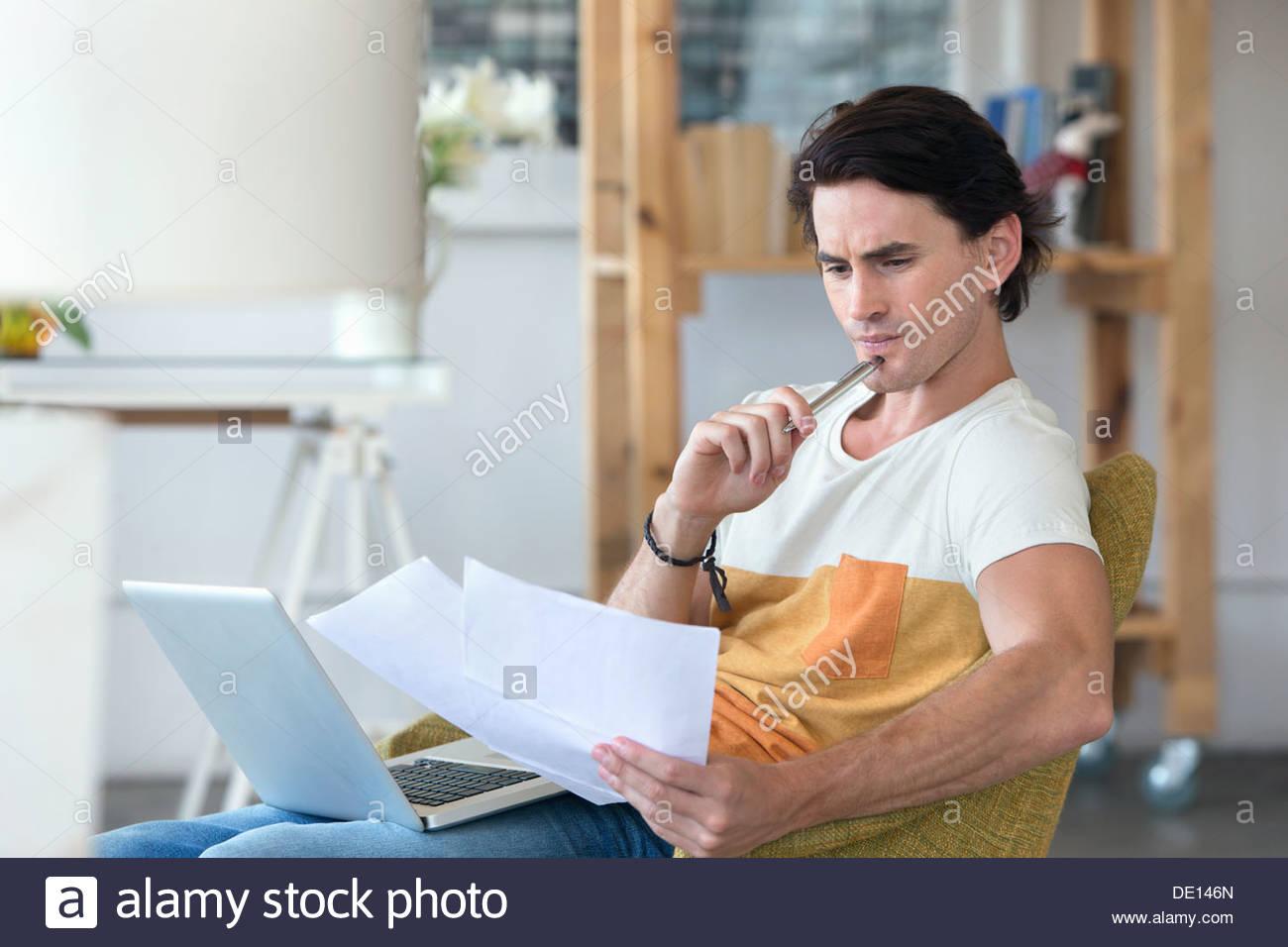 Betroffenen Mann mit Laptop blickte auf Schreibarbeit im Sessel Stockbild