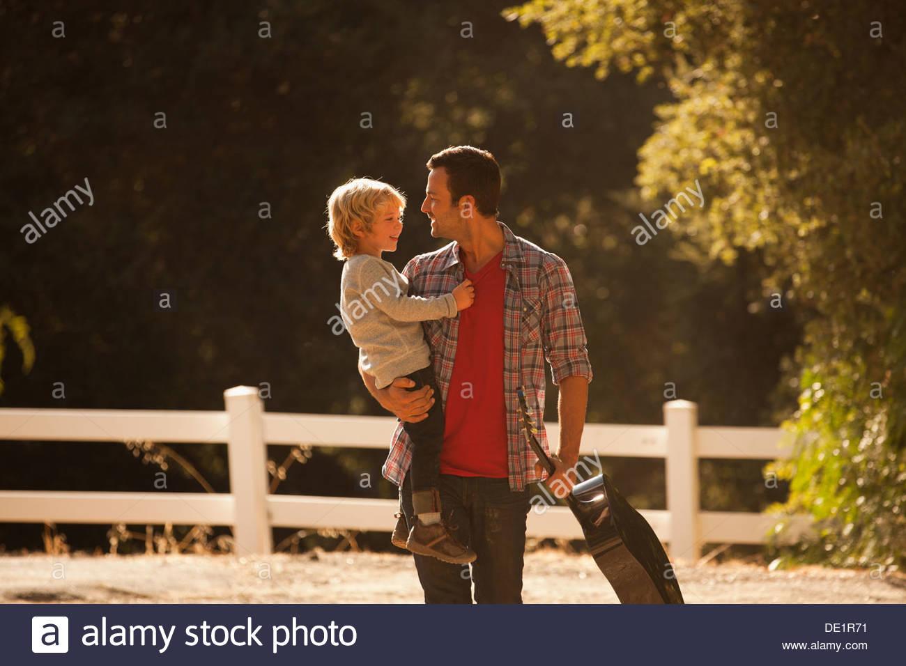 Vater mit Sohn und Gitarre auf Feldweg Stockbild