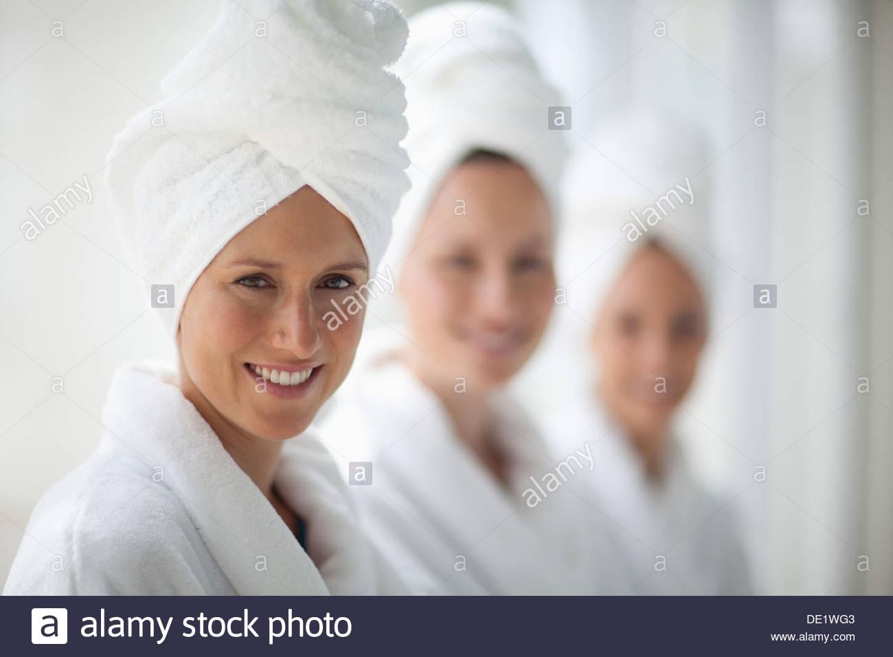 Porträt von lächelnden Frauen in Bademäntel und Haare gewickelt in Handtücher im spa Stockbild