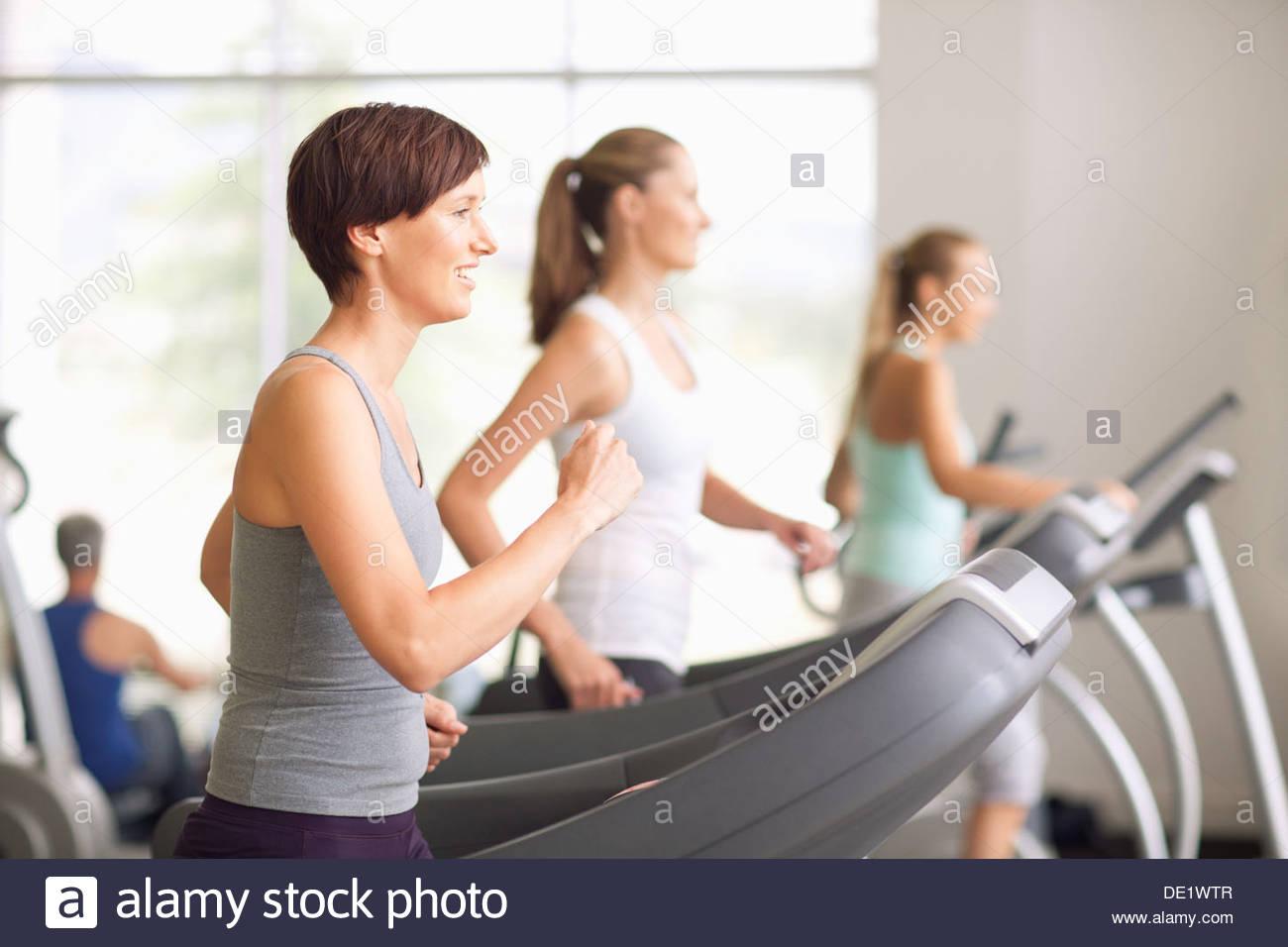 Porträt von lächelnden Frauen laufen auf Laufbändern im gymnasium Stockbild