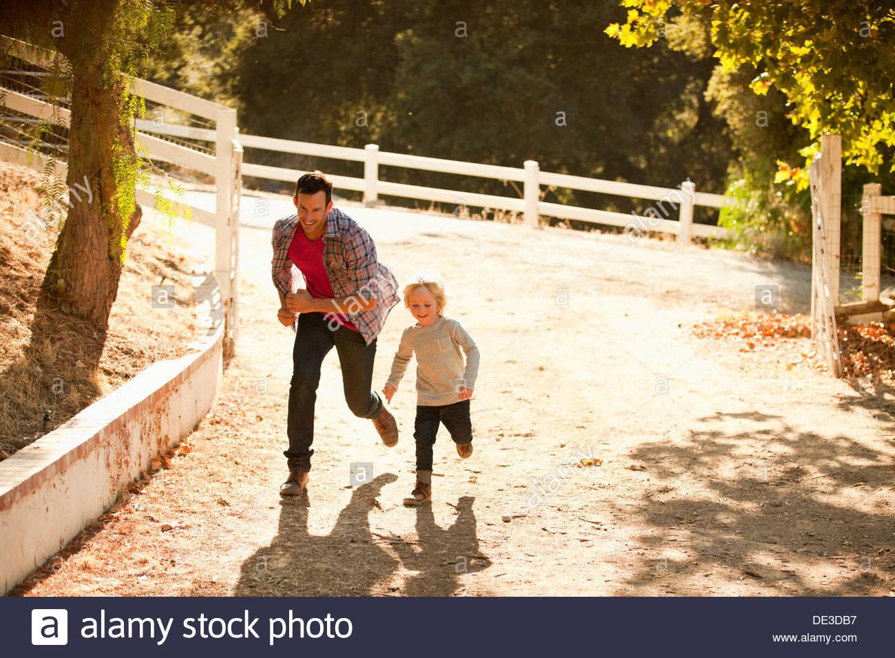 Vater jagt Sohn auf Feldweg Stockbild