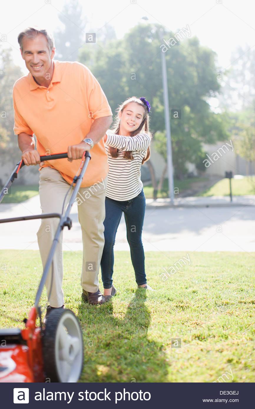 Vater und Tochter gemeinsam Rasenmähen Stockbild