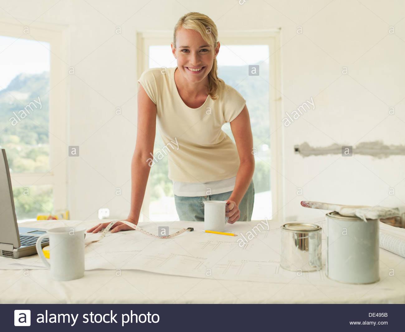 Lächelnde Frau stützte sich auf Tisch mit Blaupausen und Farbe Stockbild