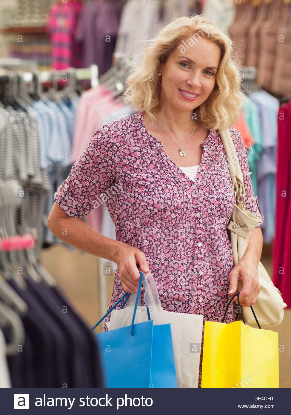 Lächelnde Frau Einkaufstaschen in Bekleidungsgeschäft Stockbild