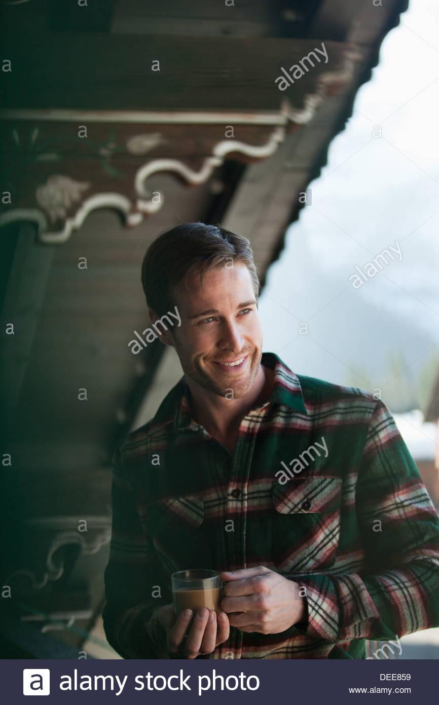 Lächelnder Mann trinken Kaffee auf der Veranda der Hütte Stockbild
