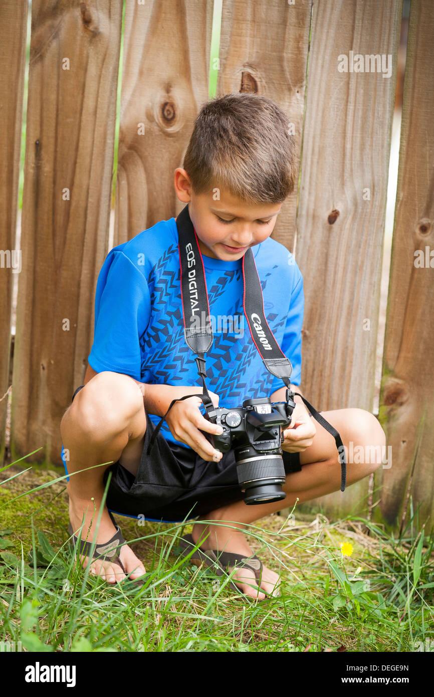 Junge in seiner Kamera schaut Stockbild