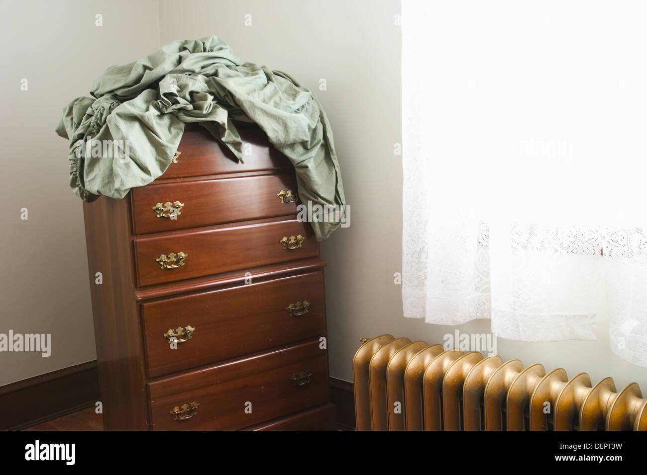 Bettwäsche-Einstellung am Anfang eines Büros, die neben ein Fenster und ein Gold - farbiges Eisen Heizkörper Stockbild