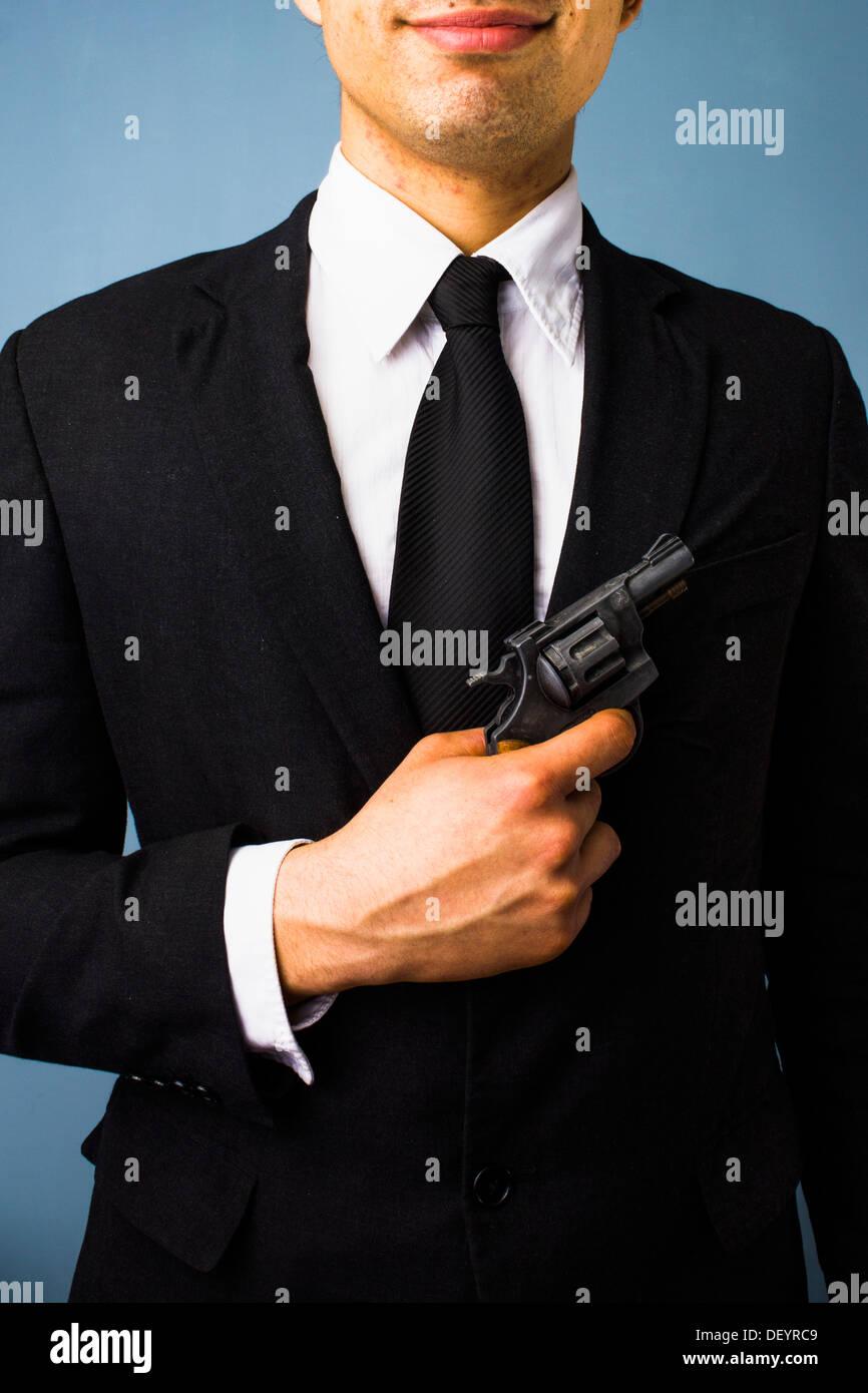 Junger Mann im Anzug ist eine Waffe halten. Stockbild