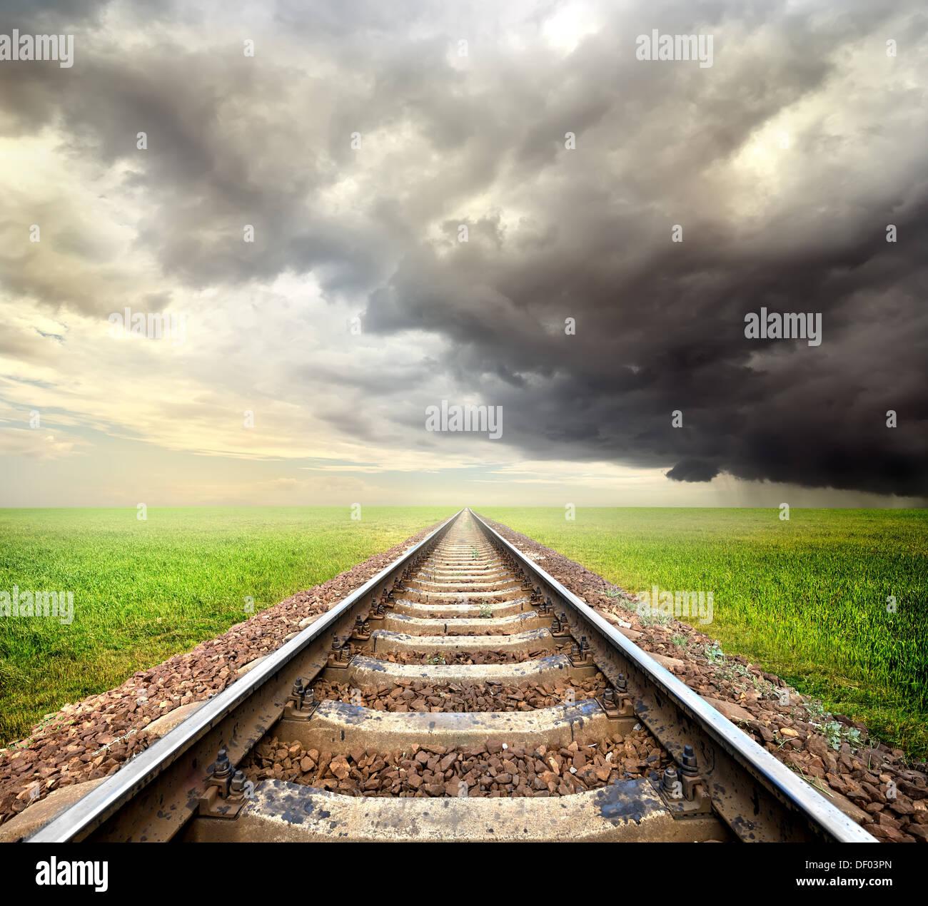 Eisenbahn in das Feld und Gewitterwolken Stockbild
