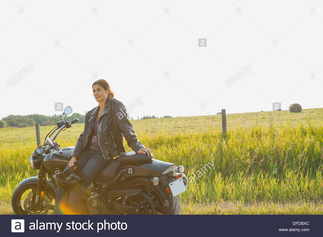 Nachdenklich weibliche Biker Motorrad gelehnt Stockbild
