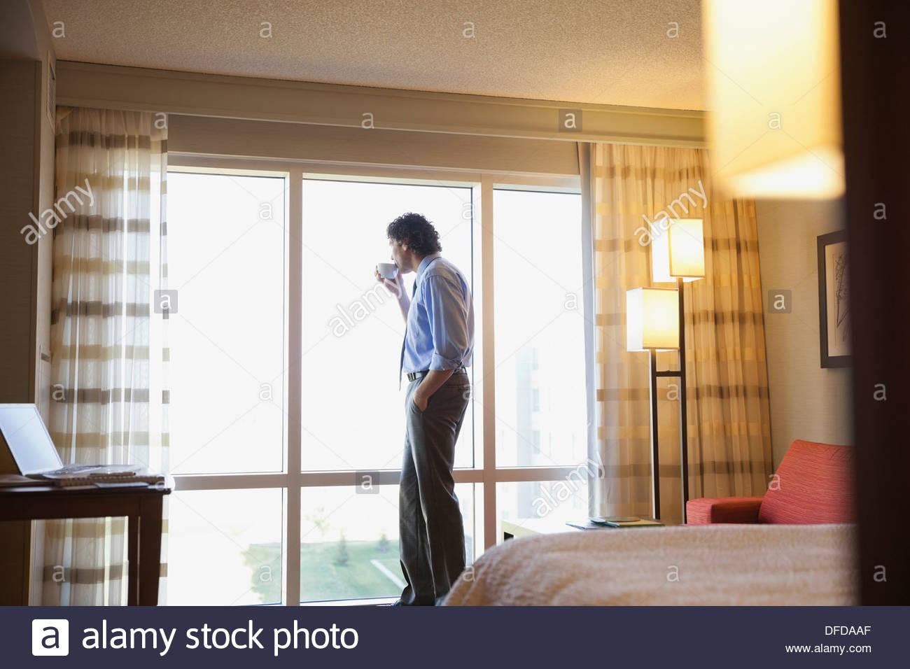 Geschäftsmann aus Hotel Zimmer Fenster mit Kaffee Stockbild