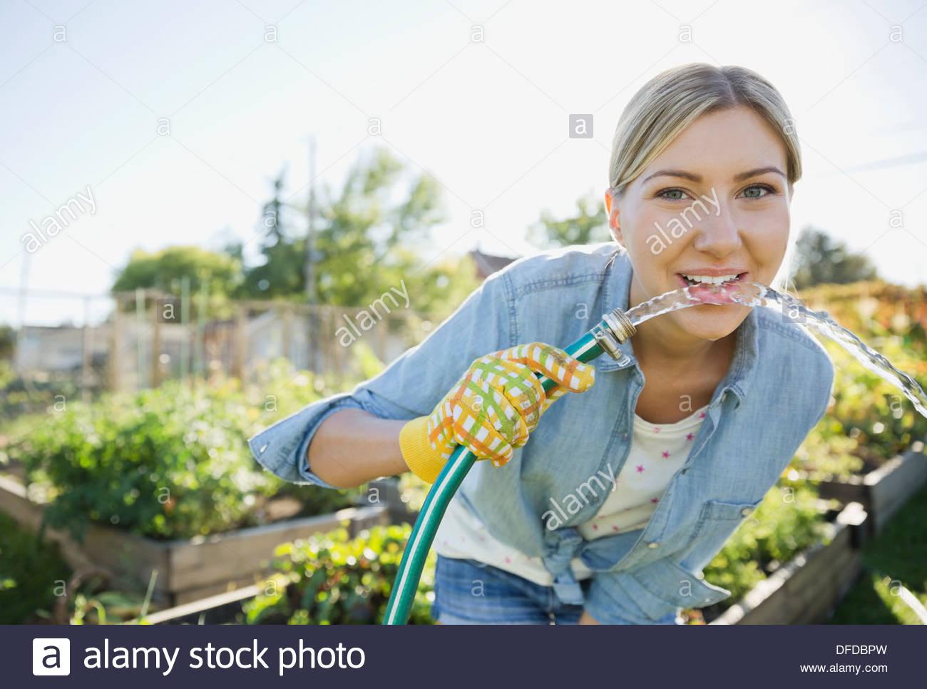 Frau um über zu trinken Wasser aus Gartenschlauch biegen Stockbild