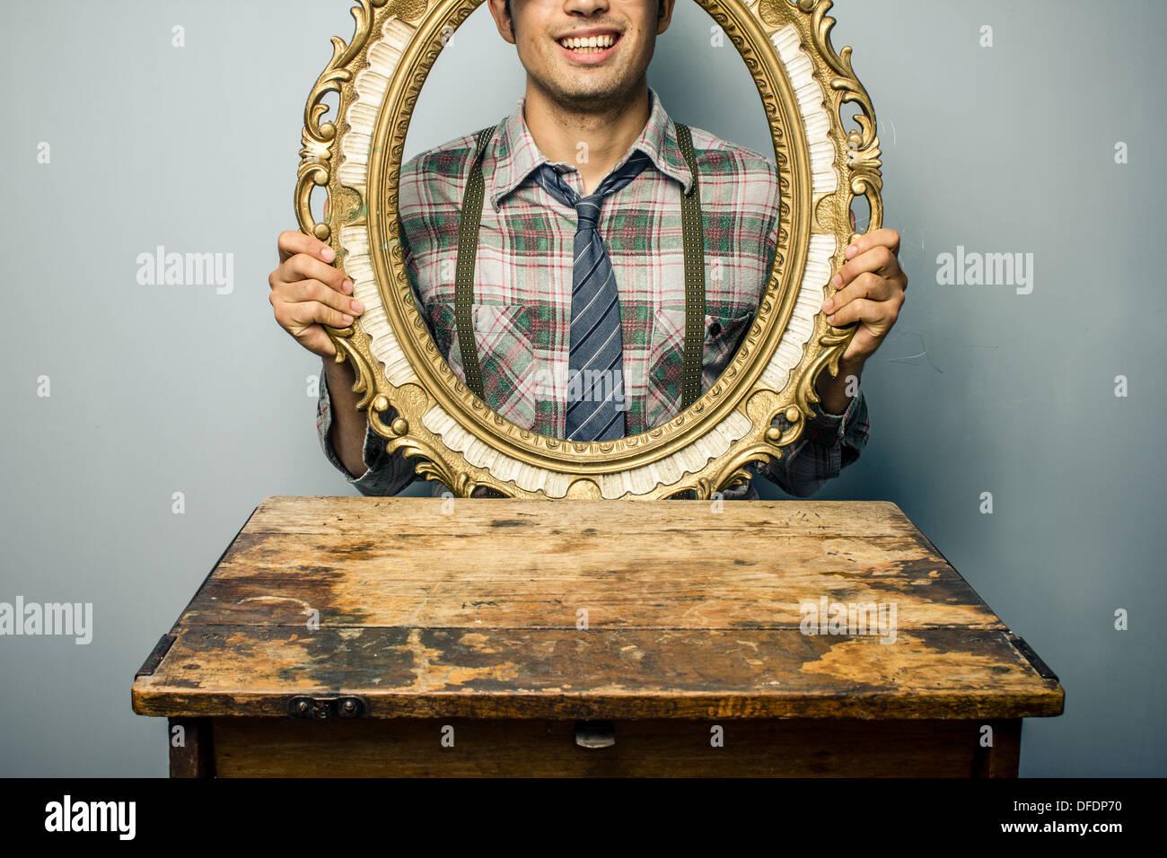 Junger Mann, Blick durch einen leeren Bilderrahmen Stockbild