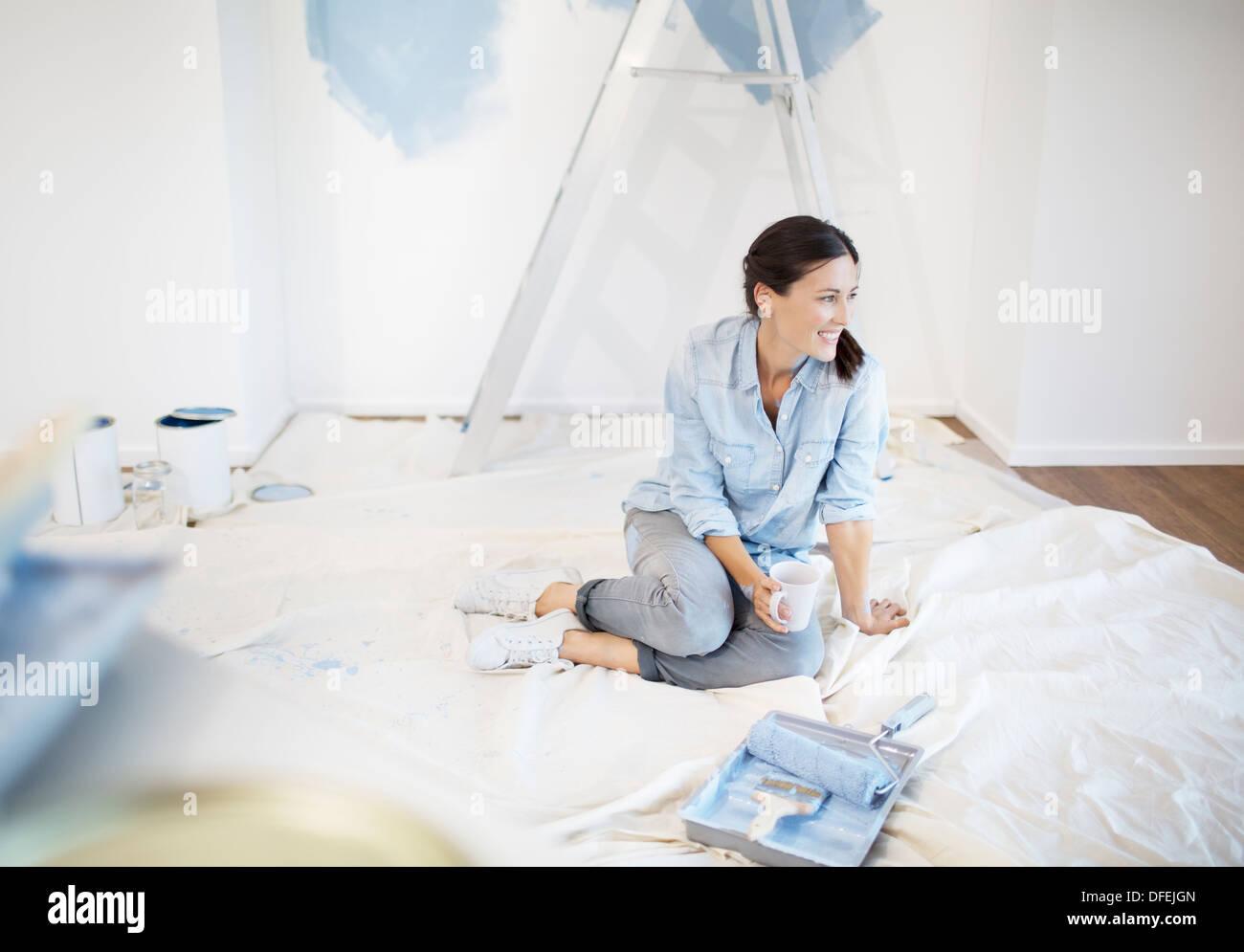 Frau trinkt Kaffee umgeben von Malerei liefert Stockbild