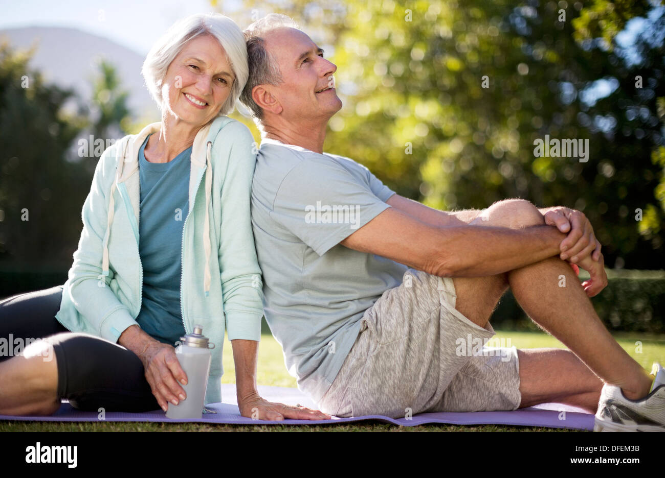 Älteres Paar auf Yoga-Matte im Park sitzend Stockbild