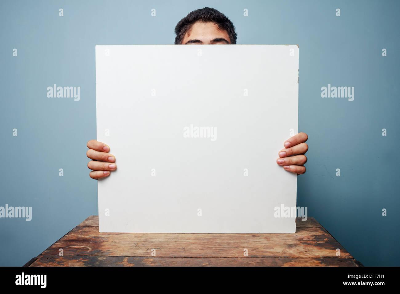 Junger Mann sitzt an einem Tisch und einem leeren weißen Namensschild, nur die Spitze des Kopfes sichtbar Stockbild