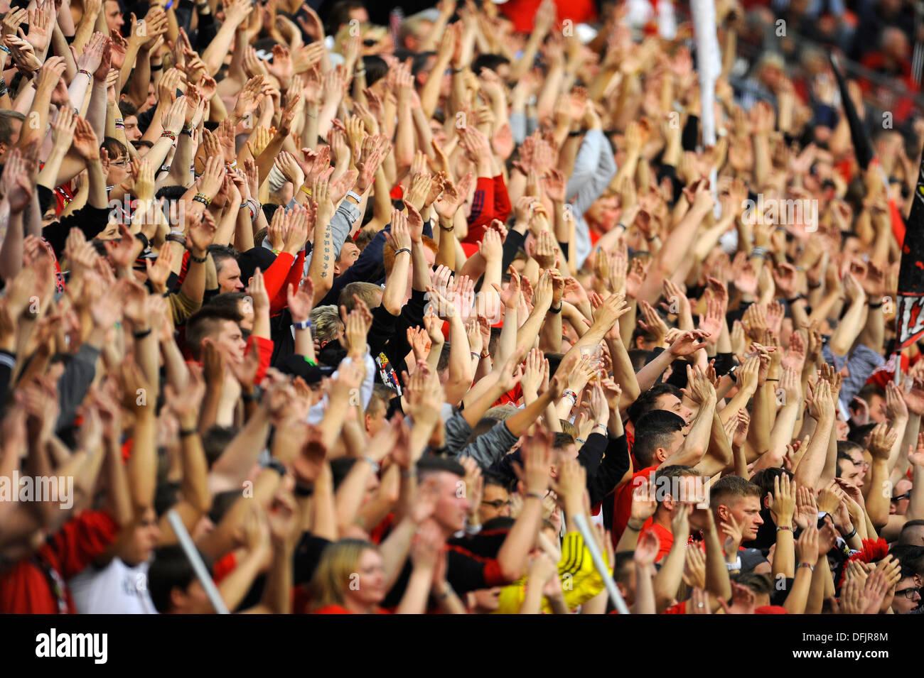Fans der deutschen Fußball-Bundesligisten Bayer 04 Leverkusen erheben ihre Hände im support Stockbild