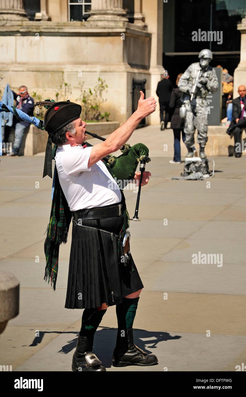 London, England, Vereinigtes Königreich. Schotte im Kilt, Dudelsack am Trafalgar Square. Menschliche Statue Stockbild