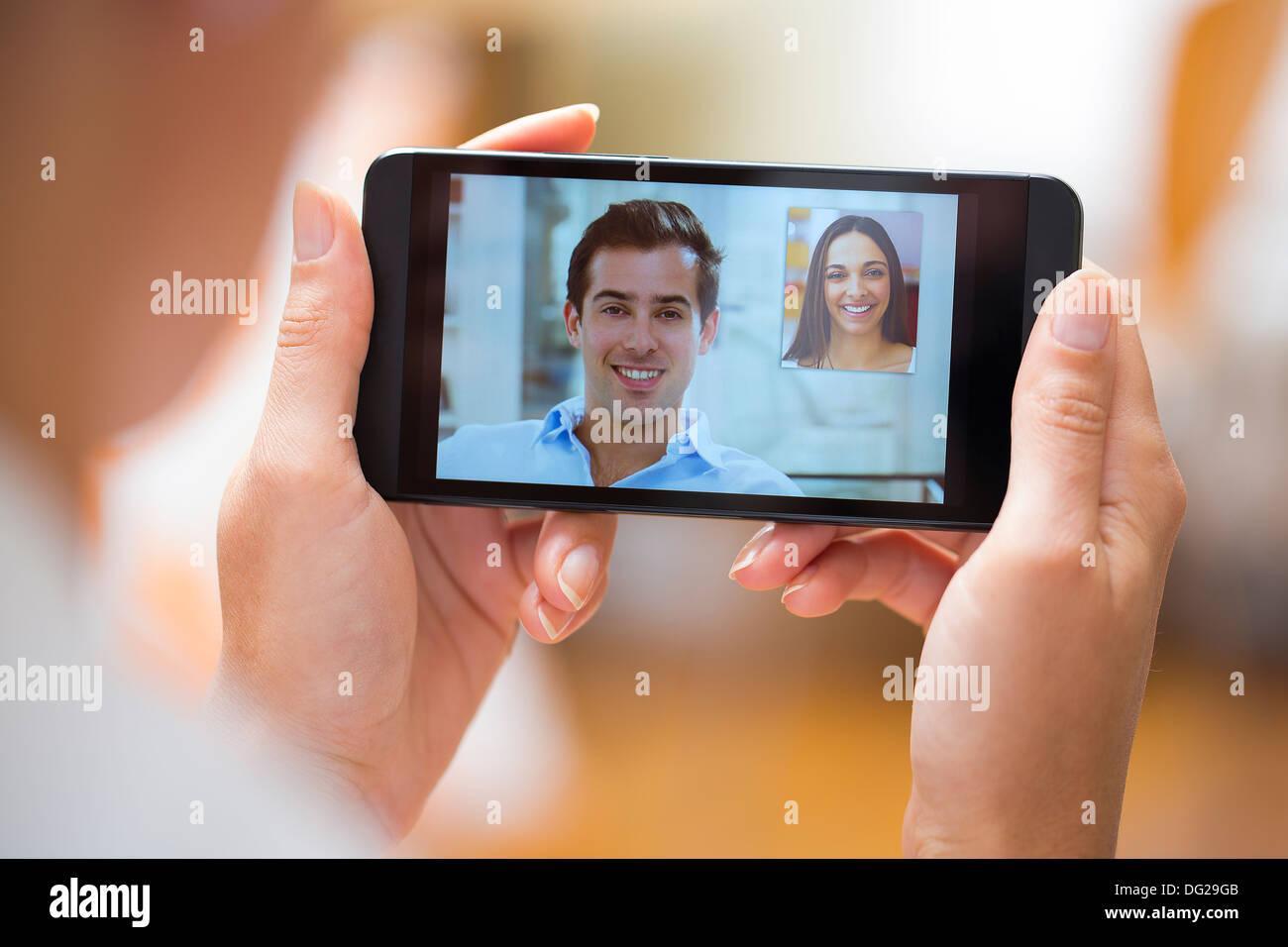 Frau mit ihrer Freundin auf Smartphone zu Hause chatten Stockbild