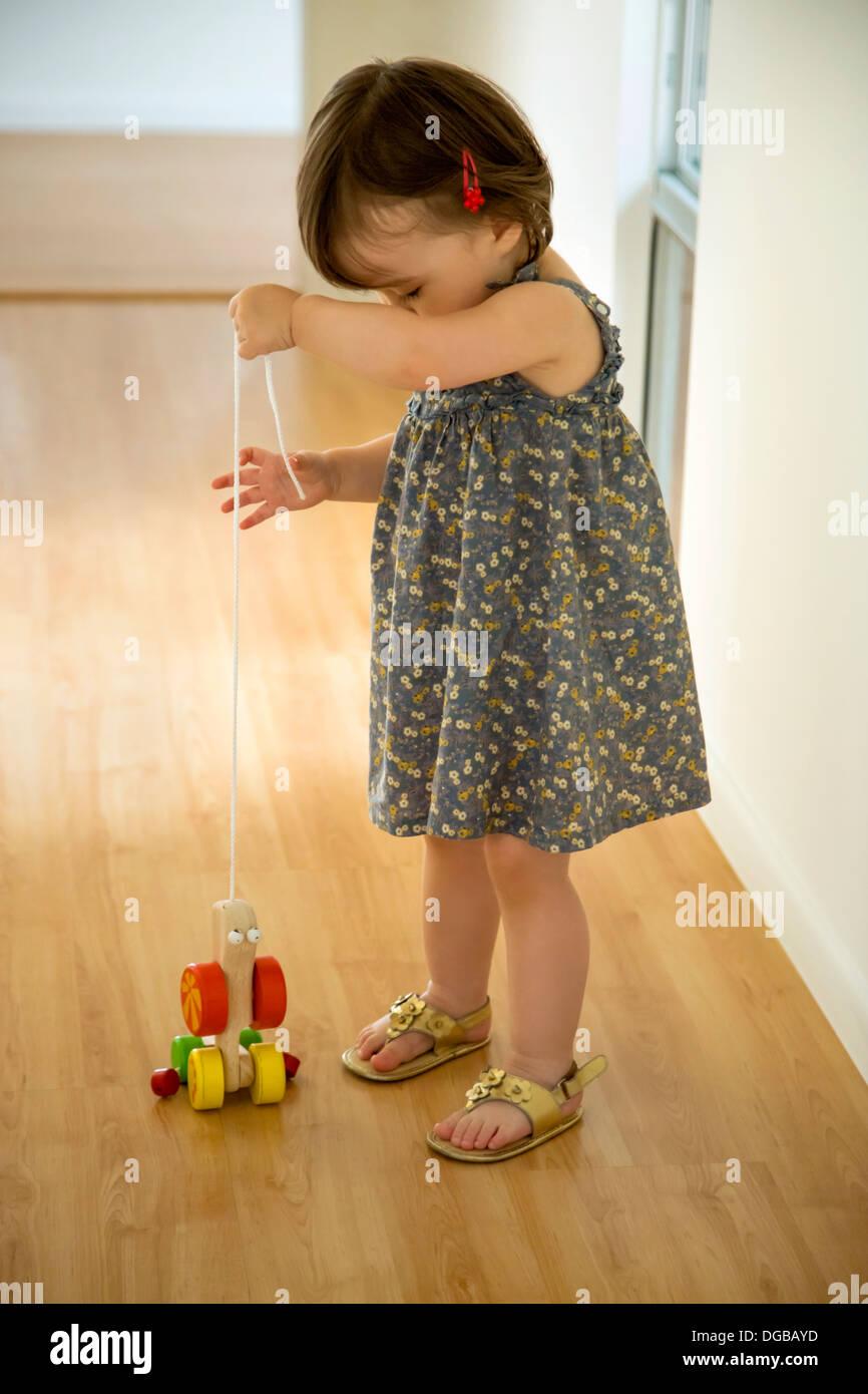 Babymädchen spielen mit einem hölzernen Spielzeug an einer Schnur Stockbild