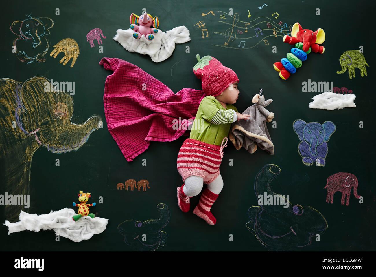 Babymädchen schläft gegen Zeichnungen auf Tafel, Draufsicht Stockbild