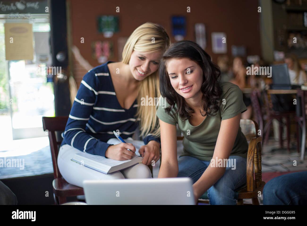 Zwei Mädchen im Teenageralter mit Lehrbüchern und Computer im café Stockbild